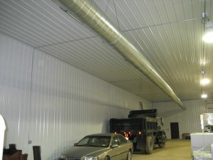 A high efficiency heating and cooling system for a storage warehouse, complete with spiral ductwork.